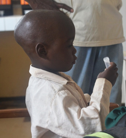 Science Scenes - child giving saliva at Cameroon lab